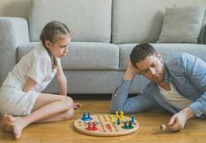 Family playing ludo. Little girl and her father playing ludo Royalty Free Stock Images