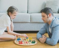 Family playing ludo. Little girl and her father playing ludo Royalty Free Stock Photography