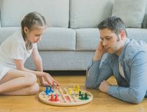 Family playing ludo. Little girl and her father playing ludo Stock Photography