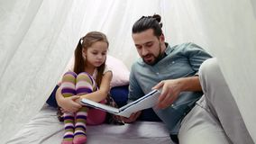 Little girl and her father reading a book together stock footage