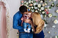 A little girl in her father`s arms did not expect kisses from her parents. The baby looks around with interest and feels stock photos