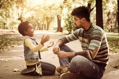 little girl and her father sitting on road in park and royalty free stock image