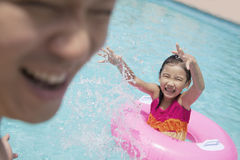 Little girl and her father splashing in the pool Royalty Free Stock Image