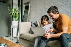 Little girl and her father using a laptop together at home.
