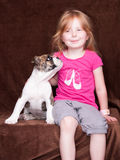 Little girl and her friend the dog look up. Little girl with a puppy, sitting in front of a brown background and the dog look up to the girl Stock Photography