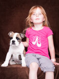 Little girl with her friend the dog. Little girl with a puppy, sitting in front of a brown background Stock Photos