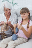 Little girl and her granddaughter knitting together Stock Image