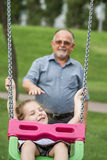 Little Girl with her Grandfather Having Fun on a Swing in a Gree Royalty Free Stock Photography