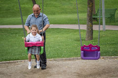 Little Girl with her Grandfather Having Fun on a Swing in a Gree Royalty Free Stock Photos