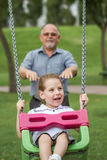 Little Girl with her Grandfather Having Fun on a Swing in a Gree Stock Photos
