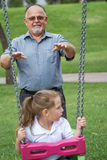 Little Girl with her Grandfather Having Fun on a Swing in a Gree Royalty Free Stock Photo