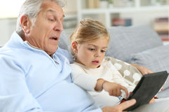 Little girl with her grandfather spendint good time with tablet Stock Image
