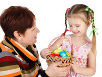 Little girl and her grandmother with basket full of easter eggs Stock Photo