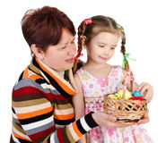 Little girl and her grandmother with basket full of easter eggs Royalty Free Stock Photo