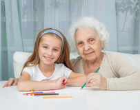 Little girl and her grandmother drawing with Royalty Free Stock Photo