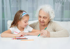 Little girl and her grandmother drawing with Stock Photography