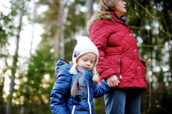 Little girl and her grandmother taking a walk in a forest Royalty Free Stock Photos