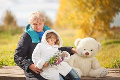 Elegant elderly woman and little girl, autumn day. Stock Photos