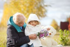 Elegant elderly woman and little girl, autumn day. Royalty Free Stock Images