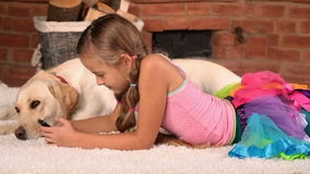 Little girl with her labrador dog, texting on the phone stock video footage