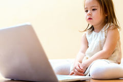 Little girl with her laptop computer Stock Image