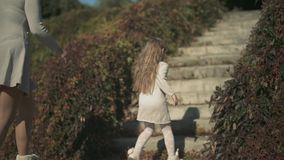 Little girl and her mom climb the stairs outdoors. Slow motion stock video