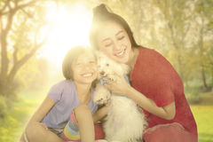 Little girl and her mom with dog at park Stock Photo