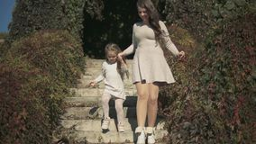 Mom and daughter go down the stairs in the park. Slow motion stock video