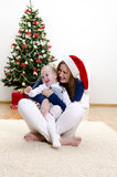 Little girl and her mom having fun at Christmas Stock Photos