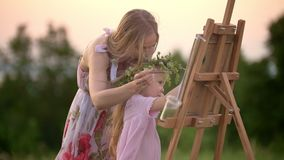 Little girl with her mom paints on easel outdoors at summer sunset stock video footage