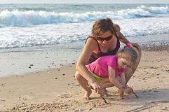 Little girl with her mom playing on the beach Royalty Free Stock Image