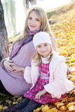 Little girl with her mother on the autumn lake Stock Photos