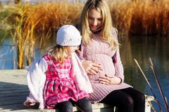 Little girl with her mother on the autumn lake Royalty Free Stock Photography