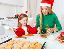 Little girl with her mother baking Christmas cookies Stock Photo