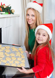 Little girl with her mother baking Christmas cookies Royalty Free Stock Photos