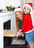 Little girl with her mother baking Christmas cookies Stock Image