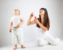Little girl and her mother blowing bubbles. Gray background Royalty Free Stock Photo