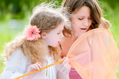Little girl and her mother with butterfly net Stock Image
