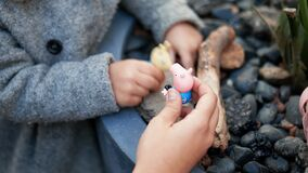 Little girl and her mother calmly playing with toys on a planter full of rocks