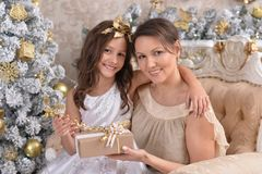 Little girl with her mother with Christmas gift. Portrait of little girl with her mother with Christmas gift Stock Image