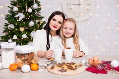 Little girl and her mother cooking and eating Christmas cookies stock photo