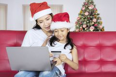 Little girl and her mother with credit card. Christmas holiday concept. Little girl with her mother using a credit card for shopping online and sitting at home Royalty Free Stock Images