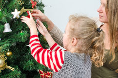 Little girl and her mother decorating tree Royalty Free Stock Photos