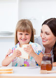 Little girl and her mother eating slices of bread Stock Images
