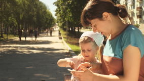 Little girl and her mother enjoying a phone sitting on a bench in the park. Young woman and her daughter are playing using the application on the phone in the