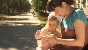 Little girl and her mother enjoying a phone sitting on a bench in the park
