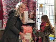 Festive Charity Donation Boxes. Little girl and her mother are giving donation boxes to a charity for christmas stock images