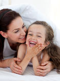 Little girl and her mother having fun on bed Royalty Free Stock Photo