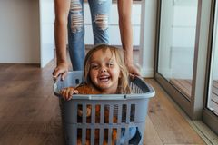 Little girl and her mother having fun doing laundry. Beautiful little girl sitting in a washing basket being pushed by her mother. Cute little girl and her stock images