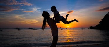 Little girl and her mother having fun at sunset on Royalty Free Stock Image